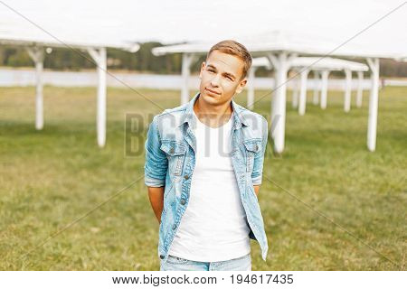 Young Man In A Denim Jacket And White T-shirt Posing On Nature
