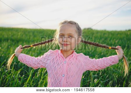 little girl with plaited long hair braids smiling portrait outdoor. Girl six years.