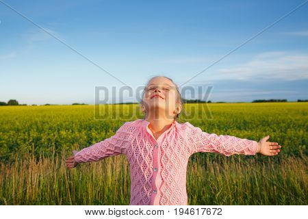 a little girl with extended arms in front of a canola field