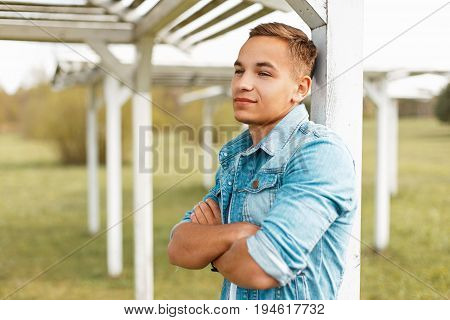 Handsome Young Man In A Stylish Denim Jacket Near Wooden Beach Canopy.