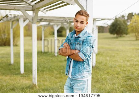 Handsome Man In Jeans Clothes Near A Wooden White Canopy In The Nature