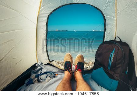 Hiker Man Sitting In A Tourist Tent by The Sea Summer Beach Holiday Vacation Concept. View Of Legs. Point Of View Shot