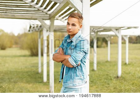 Handsome Young Fashionable Man In Jeans Clothes Stands Near A Beach Canopy