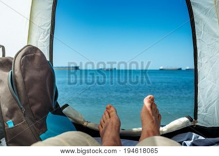 Hiker Man Lying In Tent With A View Of Sea Summer Beach Holiday Vacation Concept. View Of Legs. Point Of View Shot