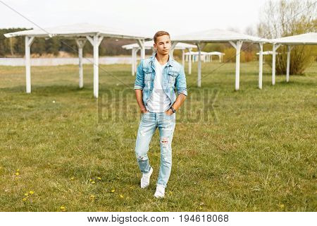 Handsome Man In Stylish Denim Clothing And A White T-shirt, Sneakers Walking On The Beach With White