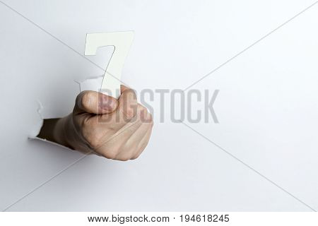 Female Hand Holding Up The Number Seven A White Background.