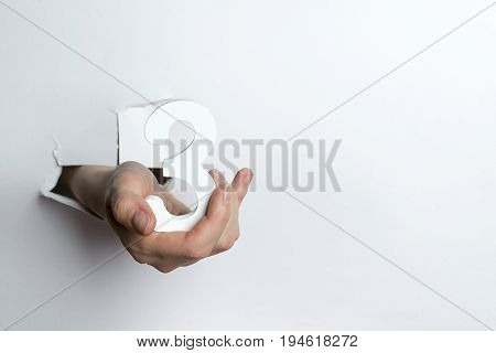 Female Hand Holding The Number Three A White Background.
