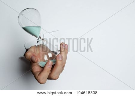 Female Hand Holding Hourglass On White Background.
