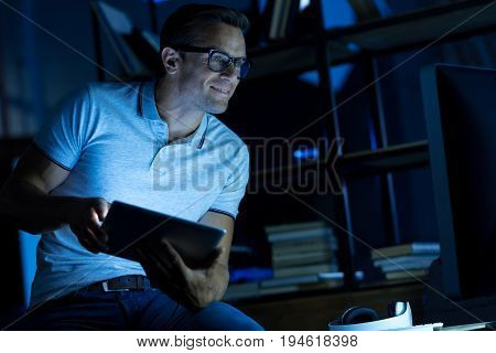 Specialist in action. Savvy bright intelligent man spending the evening in the office and using a few sources while working on his personal project