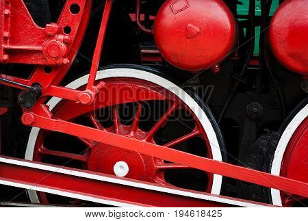 Warsaw Poland a museum of old retro steam locomotives. In the frame of the steam locomotive wheel. Color red black white
