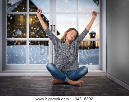 The pretty girl smiles and pulls his hands up while sitting on the floor. Large window. The snow outside the window of a village house and snowdrifts