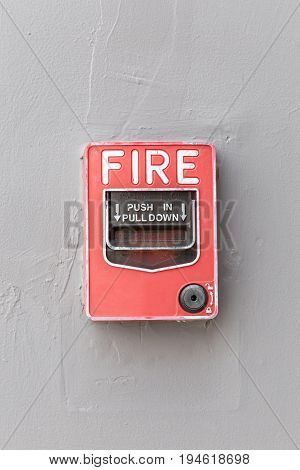 Red fire alarm switch on exterior cement wall of commercial building safety concept.
