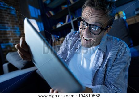Expressive gamer. Energetic young passionate guy spending his evening trying passing the level while playing with his gadget