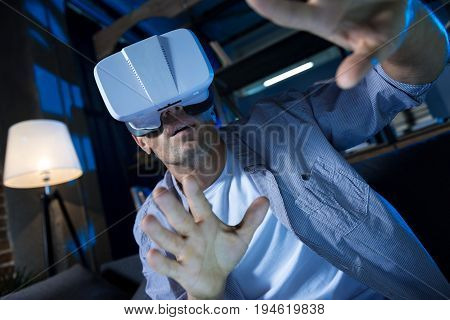 Almost feasible. Committed curious savvy guy testing his virtual reality gear while exploring different worlds and enjoying his experience