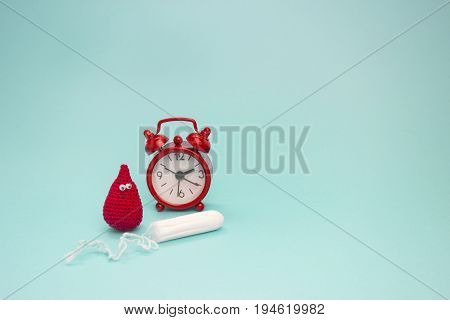 Smile crochet blood drop menstrual tampon and red alarm clock. Menstruation sanitary woman hygiene. Woman critical days gynecological menstruation cycle. Medical conception photo