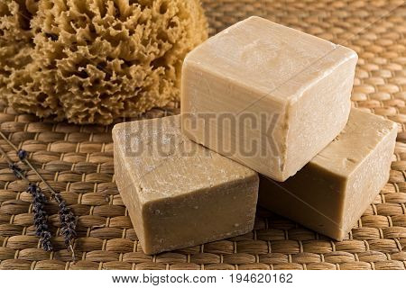 Handmade olive oil soaps, together with a natural sea sponge and a small branch of lavender