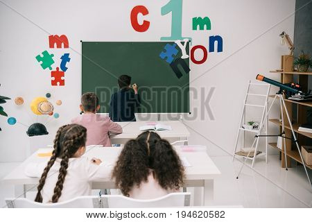 Back View Of Pupils Sitting At Desks And Looking At Classmate Writing On Chalkboard