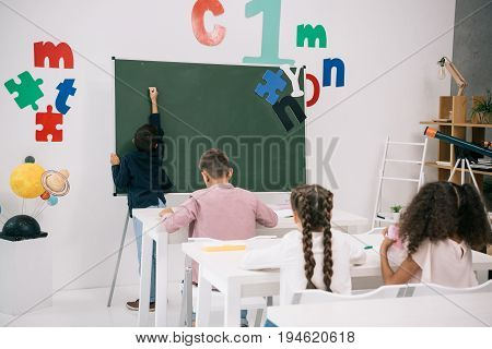 Back View Of Schoolboy Writing On Chalkboard While Classmates Studying At Desks