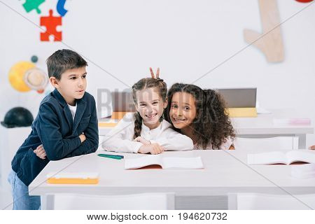 Adorable multiethnic schoolkids having fun while sitting at desk in class