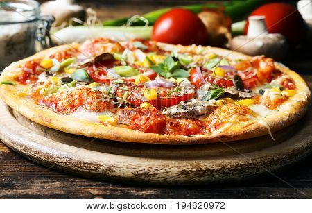 Homemade pizza with vegetables and fresh herbs