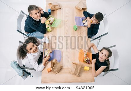 Overhead View Of Multiethnic Schoolkids Eating Lunch While Sitting At Table And Smiling At Camera