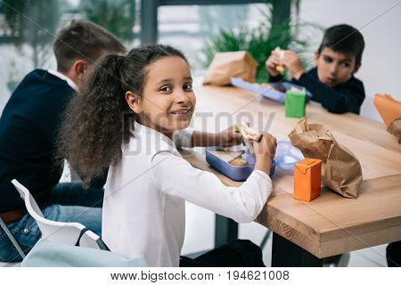 Cute Multiethnic Schoolkids Eating Lunch While Sitting At Table