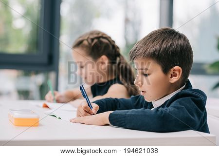Close-up Portrait Of Classmates Sitting At Desk And Writing In Exercise Books