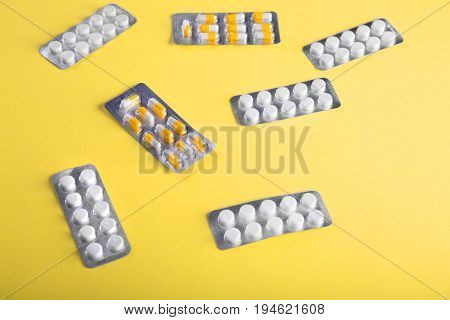 Close-up of medication on a bright yellow background. Tablets in blisters: painkillers, antibiotics, vitamins, drugs, aspirin and other.  Pharmaceutical medicament, care in container for health.