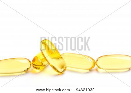 Row of golden soft gelatin capsules common use for natural essential oil supplements isolated on white background.