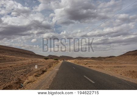 Road Through Morocco Steppe Landscape With Trees And Mount At Background. Area Between Atlas Mountai