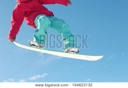 Low section of male snowboarder jumping against blue sky