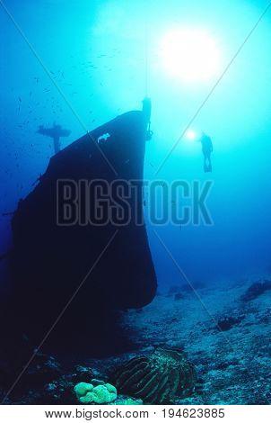Underwater shoot of female scuba diver exploring sunken ship