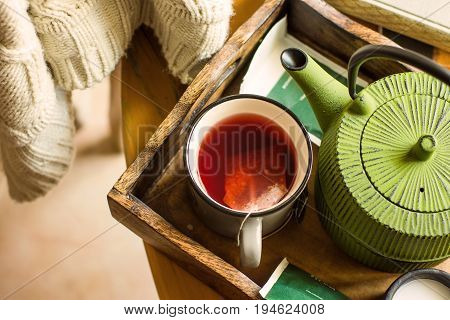 White knitted sweater hanging over wooden chair mug with red fruit tea pot in tray by bi window autumn fall mood cozy
