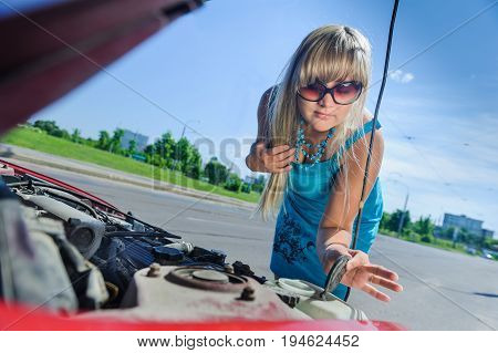 Sad attractive blonde in front of her car broken down car, assistance concept. Upset woman emotionally reacting on overheated car standing on the roadside with the open hood.
