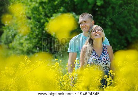 Happy couple in yellow rape field. Beautiful young girl, having fun in flower field on summer day. Just married, young family, spending time together, romantic relationship, romance and love concept