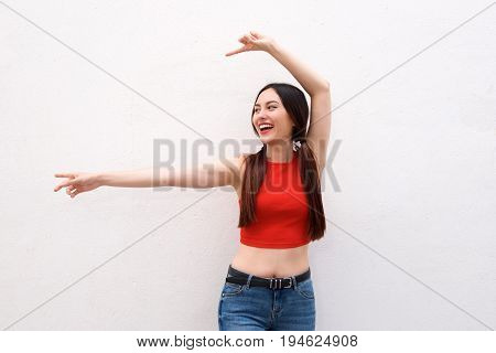 Happy Woman Indicating To The Side With Arms Outstretched