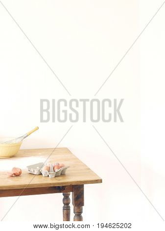 Bowl, eggs and flour scattered on table