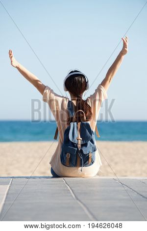 Rear Of Woman With Arms Outstretched By Sea With Headphones
