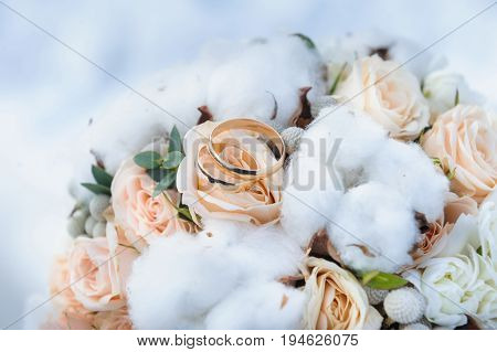 Wedding rings on beautiful elegant wedding bouquet of roses and cotton. Winter wedding bouquet. Beautiful gold wedding rings
