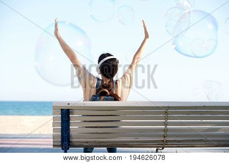 Rear Of Woman With Arms Outstretched By Sea With Bubbles