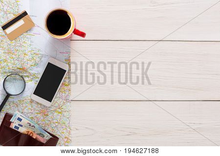 Travel planning top view background. Booking tickets online, white wood with copy space, preparation for vacation, tourist stuff on map