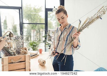 Beautiful Female Decorator Working With Dry Flowers At Workplace