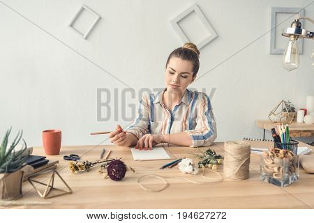 Attractive Female Decorator Working At Table With Dry Flowers
