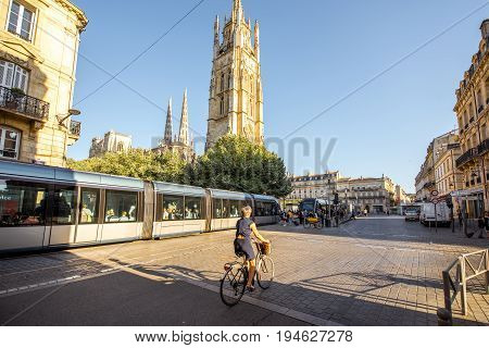 BORDEAUX, FRANCE - May 24, 2017: Morning street view with saint Pierre cathedral, tram and woman ride the bicycle in Bordeaux city, France