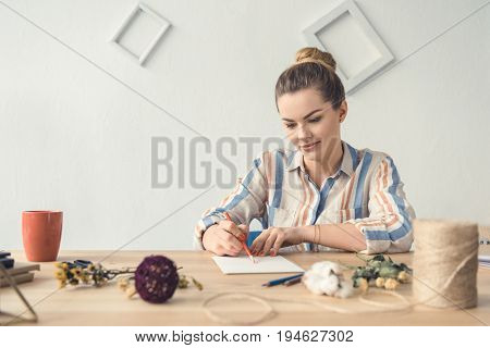 Attractive Female Decorator Writing Something While Sitting At Table With Dry Flowers