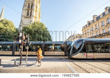 BORDEAUX, FRANCE - May 24, 2017: Morning street view with saint Pierre cathedral, trams and woman ride a bicycle in Bordeaux city, France