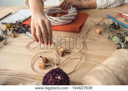 Cropped View Of Female Hands Holding Twine And White Wreath At Workplace