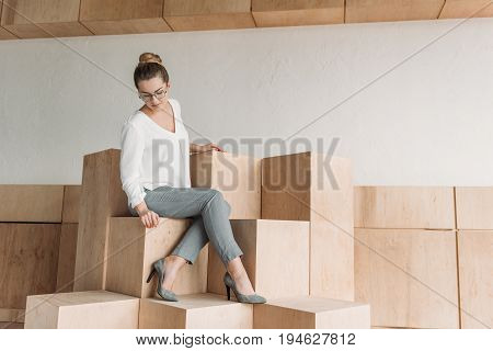 Beautiful Fashionable Businesswoman In Formalwear Sitting On Wooden Cubes