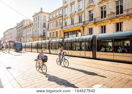 BORDEAUX, FRANCE - May 24, 2017: Street view with people ride a bicycles and modern trams in Bordeaux city during the morning in France