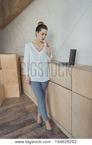 Beautiful Pensive Businesswoman Working With Laptop While Standing In Modern Office